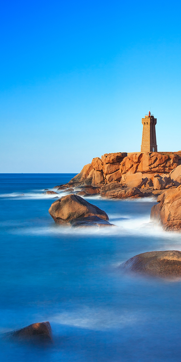 Ploumanach lighthouse sunset in pink granite coast, Brittany, France