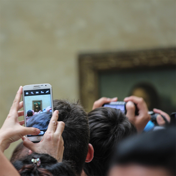 person in a crowd taking a photo of the Mona Lisa on their phone by Image Perception